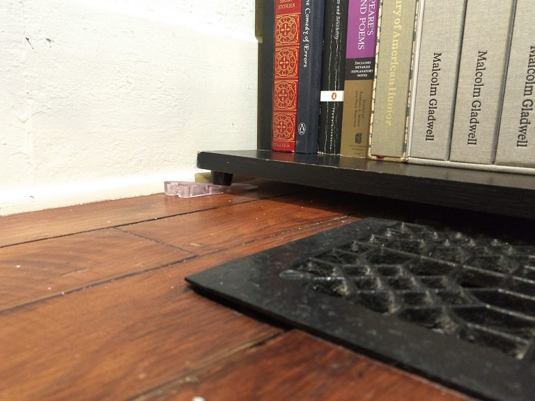 Plastic Furniture Leveler under a bookcase foot to bring it to level